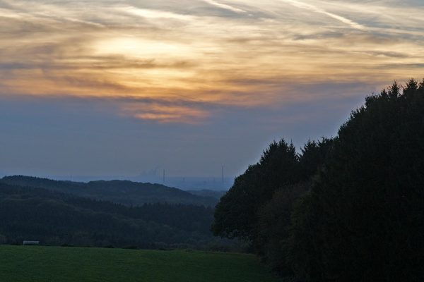 Sunday sun set in the countryside with the distant smoke stacks spewing smoke.