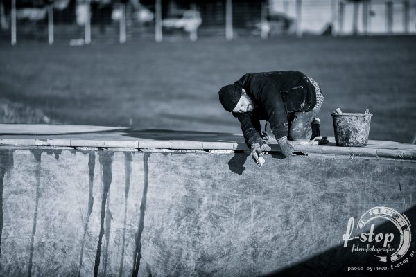 Ratman laying down pool coping.