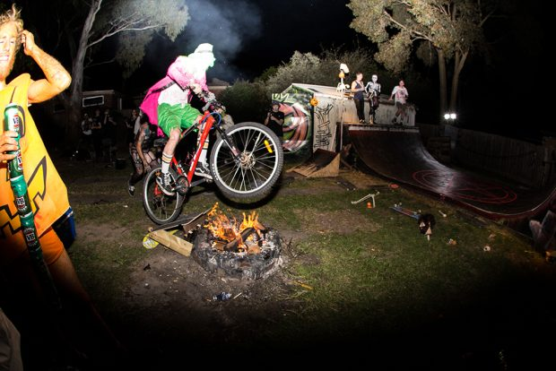 matty smith mid flight on one of many attempts to jump the fire on a bike with flat tires and doesn't pedal.